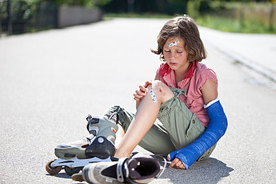 Germany, Bavaria, Wounded girl sitting on road after inline-skating accident - p30019974f by Roman Märzinger