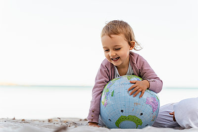 Portrait of happy little girl playing with  Earth beach ball - p300m2143692 von Daniel Ingold