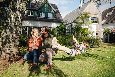 Son swinging in garden with parents next to him - p300m2167301 by Kniel Synnatzschke