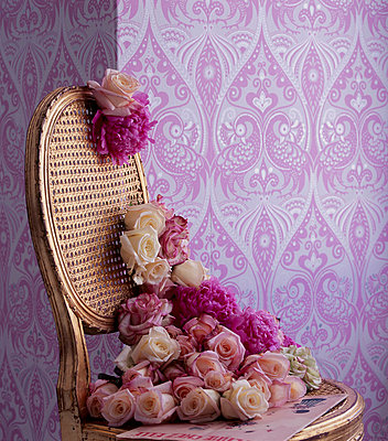 Pink bold patterned wallpaper with gold painted chair and flower display - p349m695244 by Emma Lee