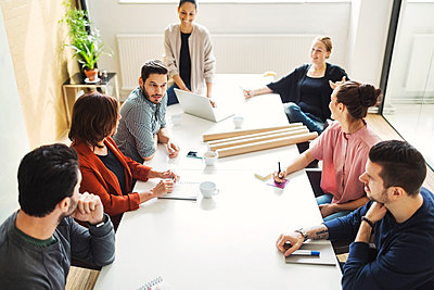High angle view of business people having discussion at table in meeting room - p426m1085666f by Maskot