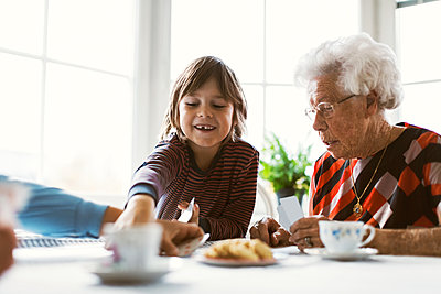 Happy boy playing cards with great grandmother and mother at table - p426m1468283 by Maskot