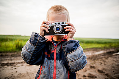 Caucasian boy taking photograph in rural field - p555m1420569 by Aleksander Rubtsov