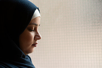 Sad Muslim woman eyes closed by the window  - p794m2215938 by Mohamad Itani