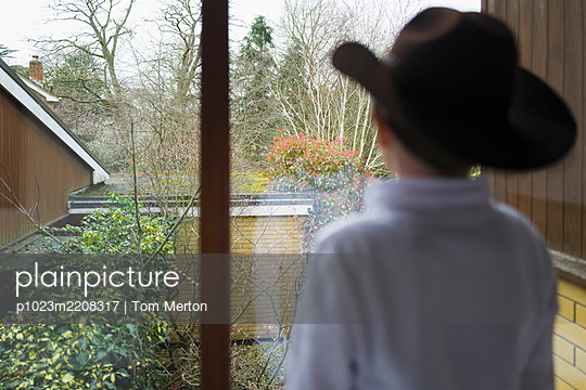 Thoughtful boy in cowboy hat looking out home window - p1023m2208317 by Tom Merton