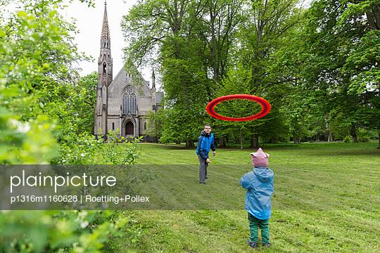 Vater und Sohn spielen Frisbee, Schlosskirche im Hintergrund, Schloss Kröchlendorff, Kröchlendorff, Uckermark, Brandenburg, Deutschland - p1316m1160628 von Roetting+Pollex