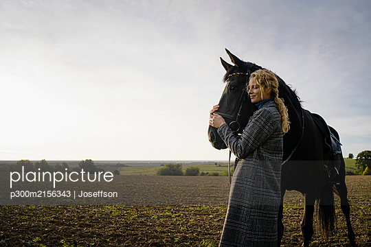 Affectionate young woman with horse on a field in the countryside - p300m2156343 by Joseffson