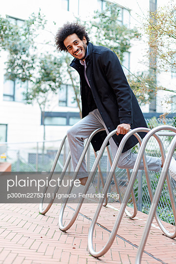 Playful young businessman balancing on bicycle rack - p300m2275318 by Ignacio Ferrándiz Roig