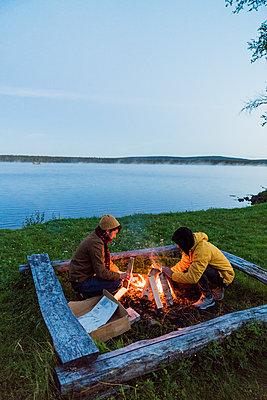 Sweden, Lapland, Two friends preparing a bonfire at the lakeshore - p300m2042285 by Kike Arnaiz