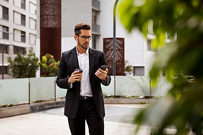 Businessman in the city checking cell phone - p300m2070391 by Mauro Grigollo