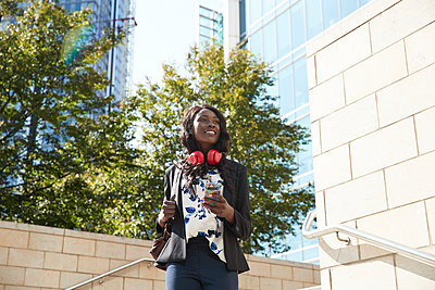 Smiling businesswoman with headphones and mobile phone carrying backpack while walking in city - p300m2241045 by Pete Muller
