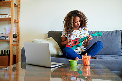 Afro young woman with laptop playing ukulele in living room - p300m2243046 by Kiko Jimenez