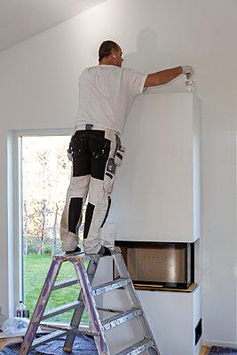 Man installing fireplace - p312m2190986 by Marie Linnér
