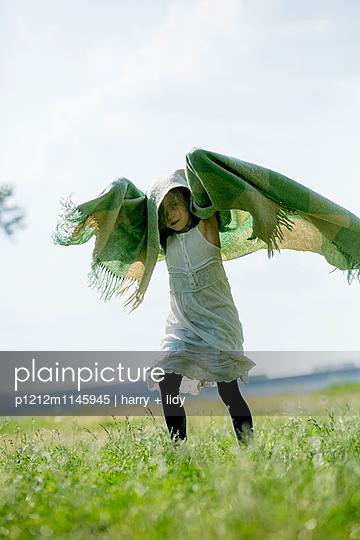 Mädchen spielt mit Wolldecke - p1212m1145945 von harry + lidy