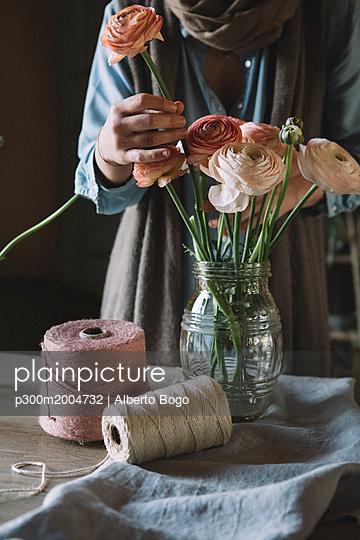 Woman arranging fresh flowers - p300m2004732 von Alberto Bogo