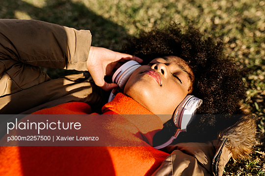 Afro woman with eyes closed listening music on grass during sunny day - p300m2257500 by Xavier Lorenzo