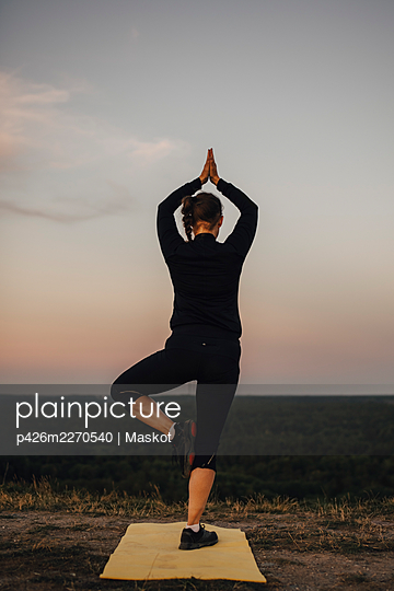 Mature sportswoman practicing tree pose against sky during sunset - p426m2270540 by Maskot