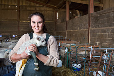 Smiling woman standing in a stable, holding a newborn lamb with bandaged front legs. - p1100m1450909 by Mint Images