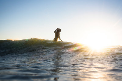Woman Surfing at Sunset - p1166m2146708 by Cavan Images