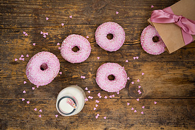 Doughnuts with pink icing and sugar granules and a bottle of milk on wood - p300m1469650 by Larissa Veronesi