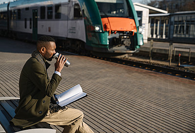 Stylish businessman drinking hot drink from reusable cup while waiting for the train - p300m2154585 by Hernandez and Sorokina