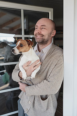 Portrait of relaxed man with dog on his arms standing at open terrace door of his house - p300m2166578 by Katharina Mikhrin