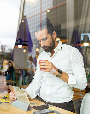 Candid portrait of bearded businessman drinking coffee in front of digital tablet inside cafe - p300m2240699 by Jose Carlos Ichiro