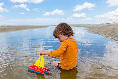 Caucasian boy sitting in water playing with toy sailboat - p555m1522946 by Marc Romanelli