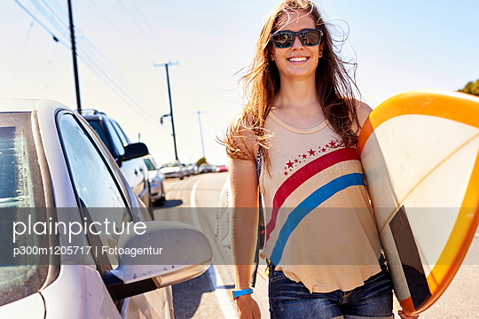 Smiling young woman carrying surfboard on coastal road - p300m1205717 by Fotoagentur