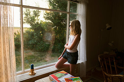 Sweden, Skane, Vejbystrand, Girl (10-11) looking though window - p352m1099944f by Mattias Ahlm