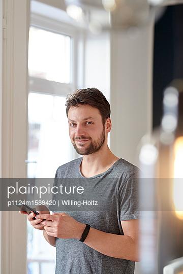 Junger Mann benutzt ein Smartphone - p1124m1589420 von Willing-Holtz