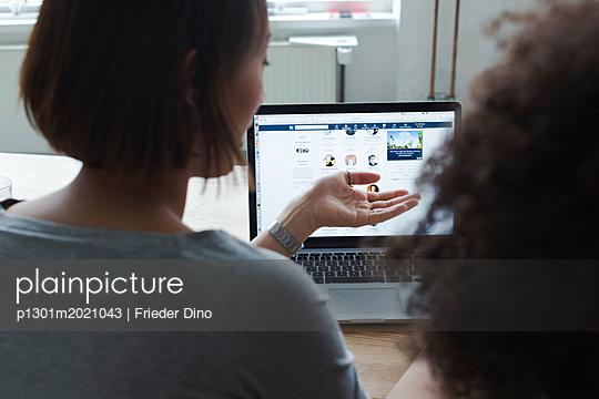 Zwei junge Kolleginnen arbeiten gemeinsam an einer Idee am Laptop  - p1301m2021043 von Delia Baum