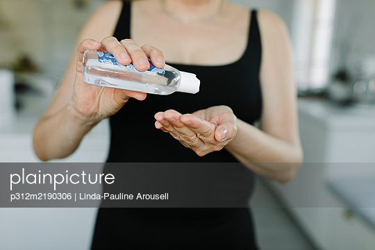 Woman applying hand sanitizer on her hands - p312m2190306 by Linda-Pauline Arousell
