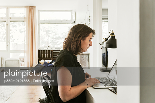 Young woman using laptop at desk - p352m2121368 by Folio Images