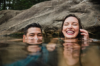 Portrait playful young couple swimming in lake - p1023m2066798 by Jarusha Brown