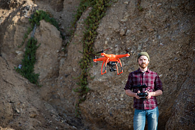 Man flying drone while standing against rock formation - p1166m1545264 by Cavan Social