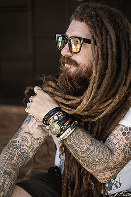 hipster guy with dreadlocks and tattoo sitting on the beach in thailan - p1166m2269085 by Cavan Images