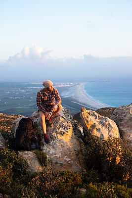 Spain, Andalusia, Tarifa, man on a hiking trip at the coast sitting on rock - p300m2080683 by Sebastian Kanzler