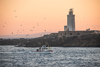 Spain, Andalusia, Tarifa, fishing boat in front of lighthouse - p300m2082980 von Sebastian Kanzler