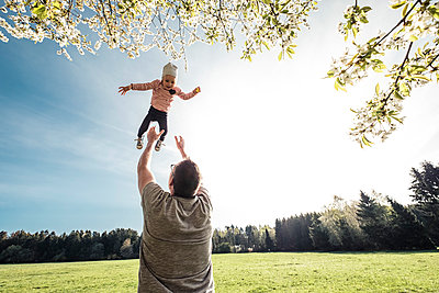 Father throwing little daughter up in air - p300m2166941 by Wilfried Feder