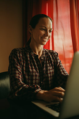 Businesswoman smiling while working on laptop in office - p300m2220644 by David Molina Grande