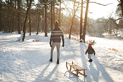 Father walking with son while pulling sled on snow during winter - p300m2281847 by Frank van Delft