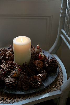Lit candle and pine cones on wicker chair seat - p349m2167796 by Polly Wreford