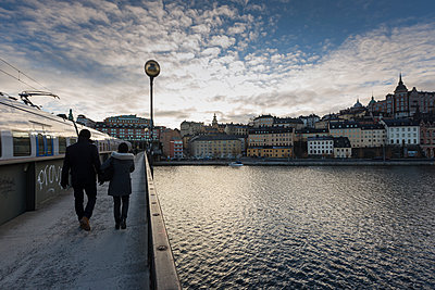 Rear view of couple walking at waterfront in Stockholm, Sweden - p352m1536573 by Calle Artmark
