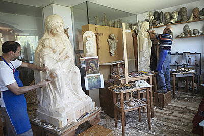 Sculptors chiseling figures from wood - p429m747168f by Stefano Gilera