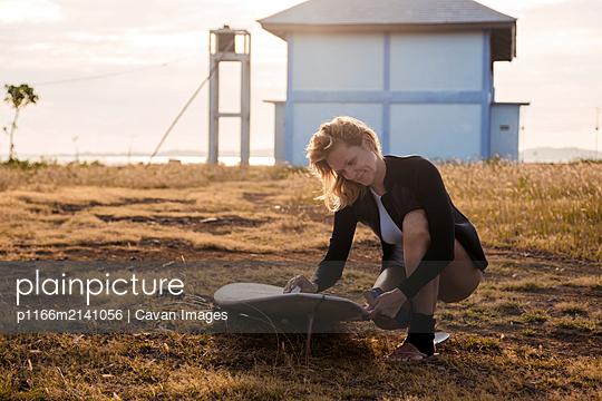 Woman preparing for surfing - p1166m2141056 by Cavan Images
