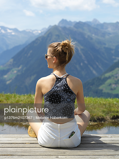 Young woman looking at mountain scenery - p1376m2107367 by Melanie Haberkorn