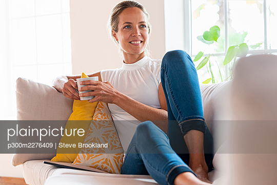 Smiling woman day dreaming while having coffee on sofa at home - p300m2276409 by Steve Brookland