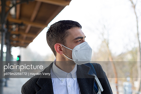 Young man with mask on the platform, portrait - p975m2259772 by Hayden Verry