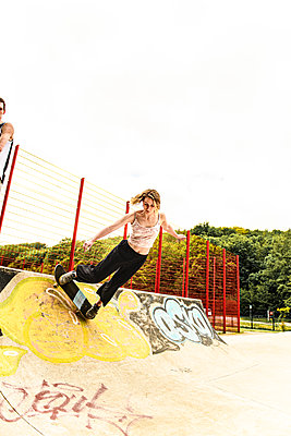 Young woman riding a skateboard in a skatepark - p1267m2288261 by Jörg Meier